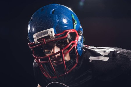 close-up portrait of serious american football player in helmet looking at camera isolated on black