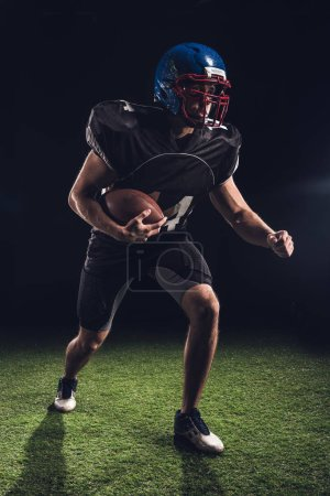 american football player holding ball and running on field on black