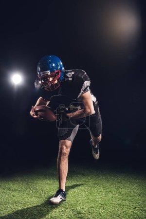 american football player holding ball and running on field under spotlights on black