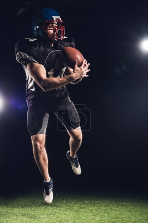 young american football player jumping with ball over green grass under spotlights on black
