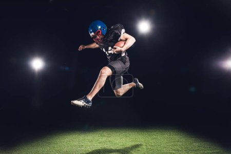 american football player jumping with ball over green grass under spotlights on black