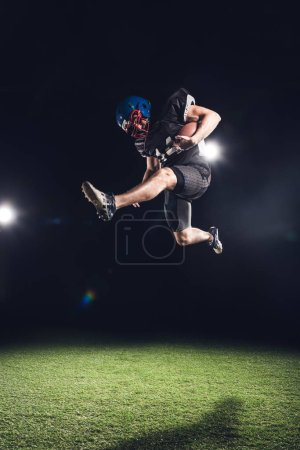 american football player jumping with ball over green grass on black