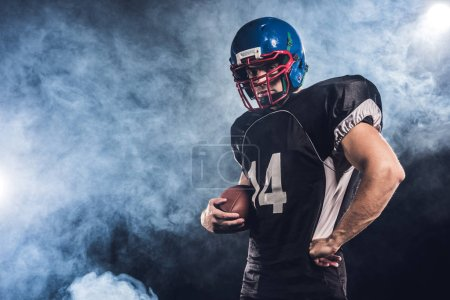 serious american football player with ball against white smoke