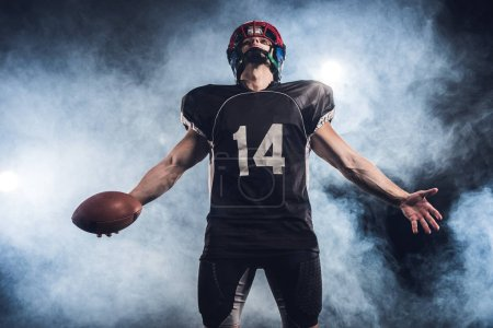 american football player with ball looking up against white smoke