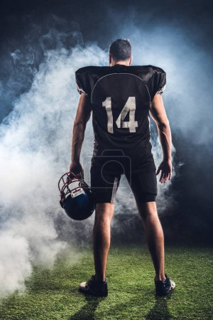 rear view of equipped american football player with helmet in hand against white smoke