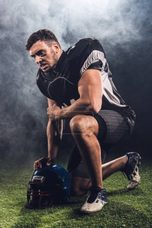 angry young american football player with helmet standing on knee on black