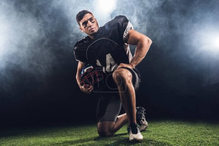 handsome young american football player with helmet standing on knee on black