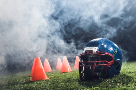 close-up shot of american football helmet with cones on green grass with white smoke above