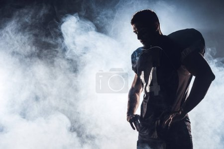 dark silhouette of thoughtful american football player looking down against white smoke