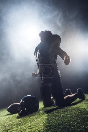 young depressed american football player looking up and shouting while standing on knees on green grass against white smoke