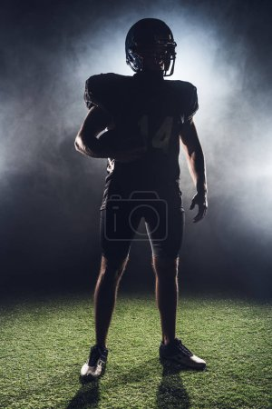 silhouette of equipped american football player with ball standing on green grass against white smoke
