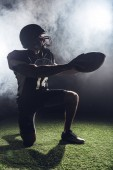 young american football player standing on knee on green grass and holding ball against white smoke