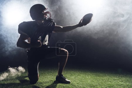 american football player standing on knee on green grass and holding ball against white smoke