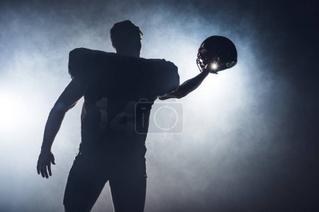 silhouette of american football player holding helmet against white smoke