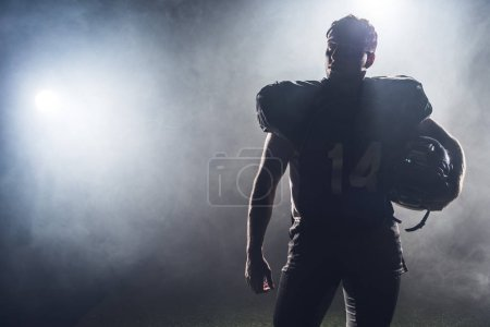 Photo for Silhouette of american football player in uniform against white smoke - Royalty Free Image