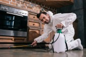 pest control worker spraying pesticides under cabinet in kitchen and looking at camera
