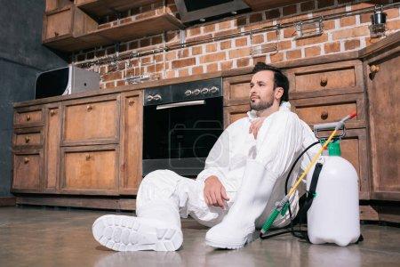 travailleur fatigué de la lutte antiparasitaire assis sur le sol dans la cuisine