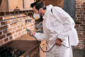 side view of pest control worker spraying pesticides under shelves in kitchen