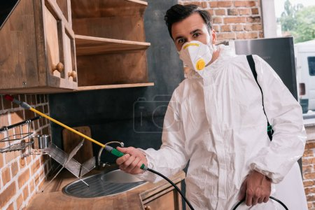 pest control worker spraying pesticides under shelves in kitchen and looking at camera