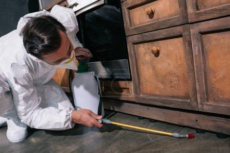 travailleur de contrôle antiparasitaire en uniforme, épandage de pesticides sous armoire de cuisine