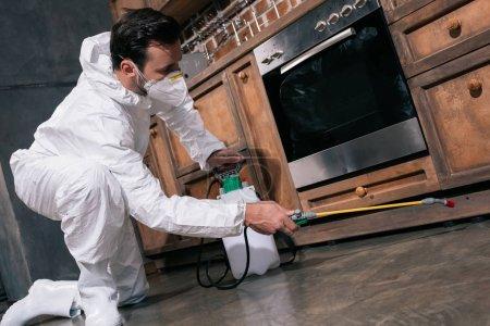 pest control worker spraying pesticides under cabinet in kitchen