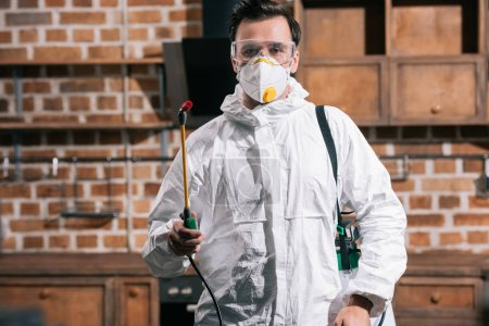 pest control worker standing with sprayer in kitchen and looking at camera