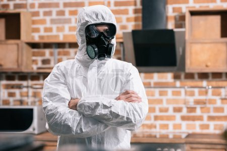 pest control worker standing in uniform with crossed arms in kitchen