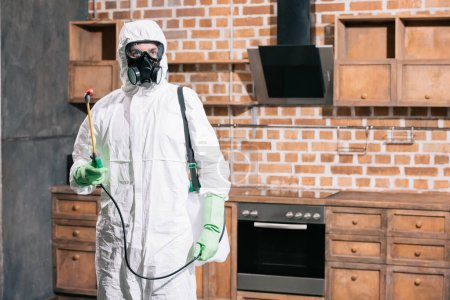 pest control worker standing with sprayer in kitchen