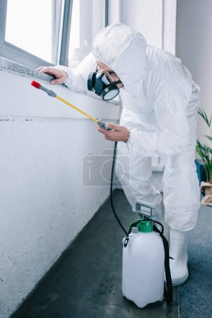 pest control worker in uniform spraying pesticides under windowsill at home