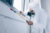 pest control worker spraying pesticides under windowsill at home