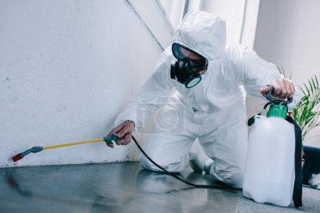 travailleur de contrôle antiparasitaires pulvérisation de pesticides sur le plancher à la maison