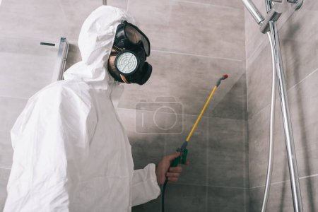 pest control worker in respirator spraying pesticides with sprayer in bathroom