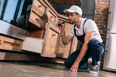 pest control worker examining kitchen with flashlight