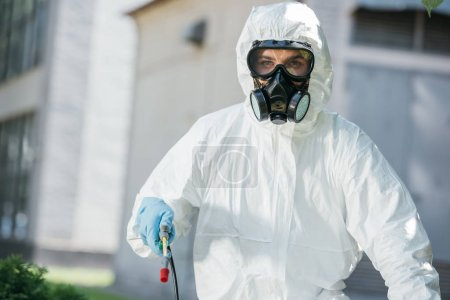 portrait of pest control worker in respirator looking at camera