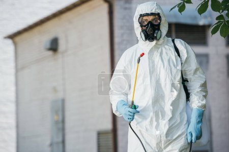 pest control worker in respirator holding sprayer