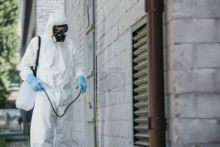 pest control worker spraying pesticides with sprayer on building wall on street