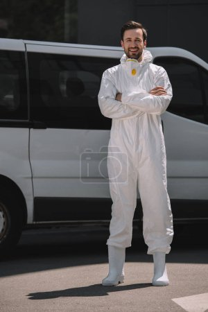 smiling pest control worker with crossed arms looking at camera near car on street