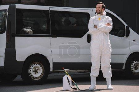 Photo pour Souriant travailleur contrôle antiparasitaire en uniforme debout avec les bras croisés près de voiture et du pulvérisateur sur la rue - image libre de droit
