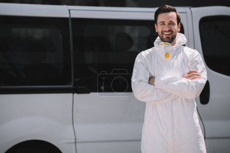 happy pest control worker in uniform standing with crossed arms near car on street