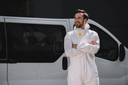 Photo for Smiling pest control worker in uniform standing with crossed arms near car on street - Royalty Free Image