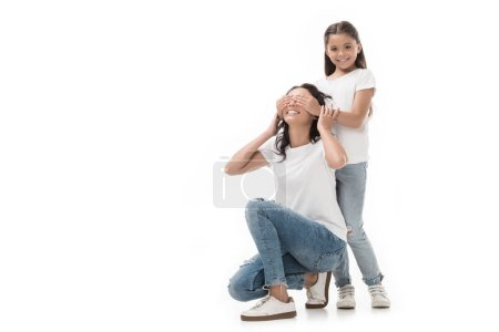 smiling kid covering mothers eyes isolated on white