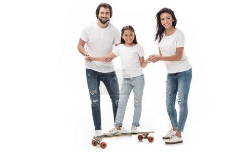 smiling parents helping daughter skating on skateboard isolated on white