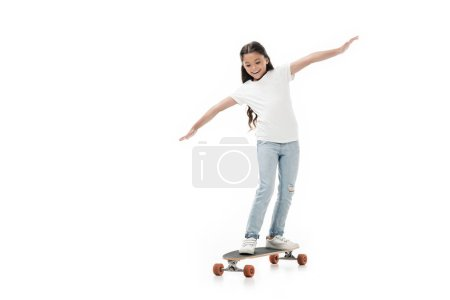 cheerful kid with outstretched arms skating skateboard isolated on white