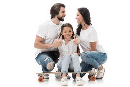 Foto de Niño sonriente sentada en patineta y mostrando los pulgares con los padres detrás de aislados en blanco - Imagen libre de derechos