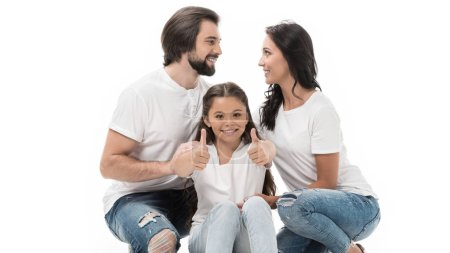 portrait of smiling kid showing thumbs up with parents behind isolated on white