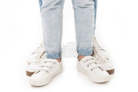 partial view of family in jeans and white footwear isolated on white