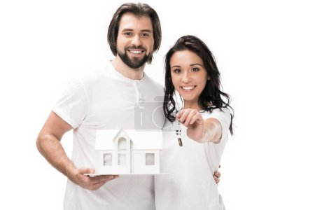 portrait of smiling couple with house model and keys isolated on white