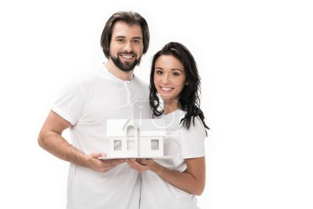 portrait of smiling couple with house model isolated on white