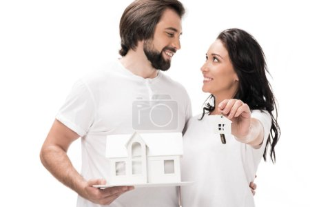 selective focus of smiling couple with house model and keys isolated on white