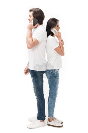 side view of couple talking on smartphones isolated on white